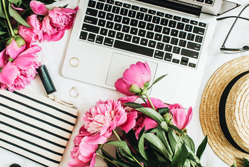 Flat lay fashion feminine office desk with laptop, pink peony flowers, cosmetics, accessories.