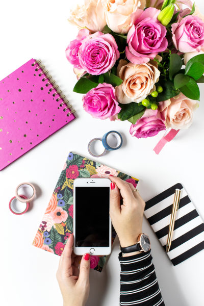 Holding iphone over planner on desk with flowers, tape, pens, and notebooks.