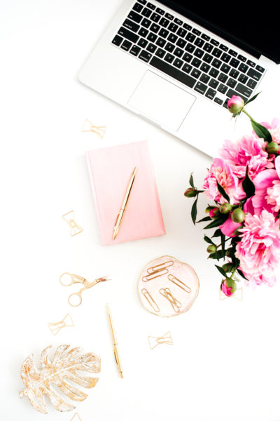 A workspace with laptop, pink peonies bouquet, golden accessories, pink diary on white background.
